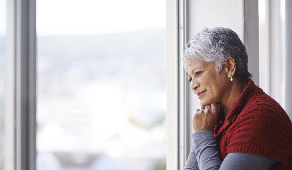 En eldre dame ser ut av vinduet