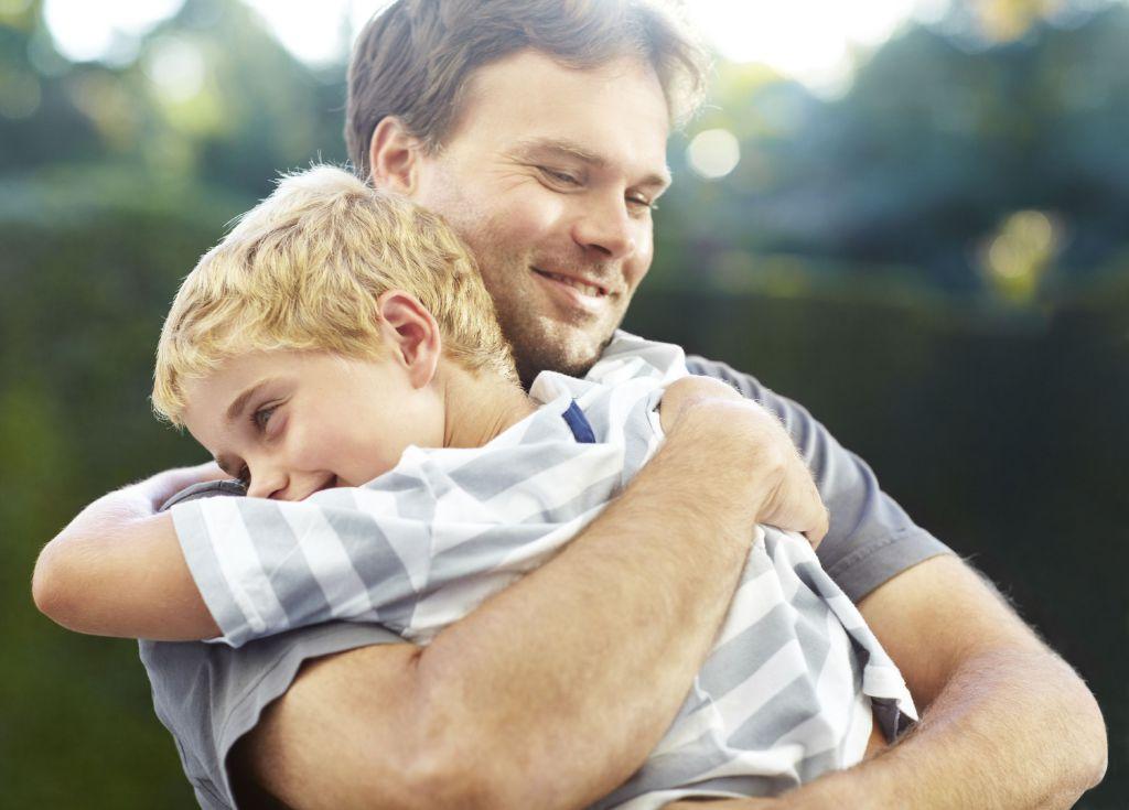 Far klemmer sin sønn, begge smiler