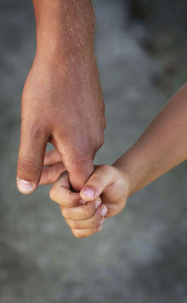Et barns hånd griper rundt en voksens pekefinger