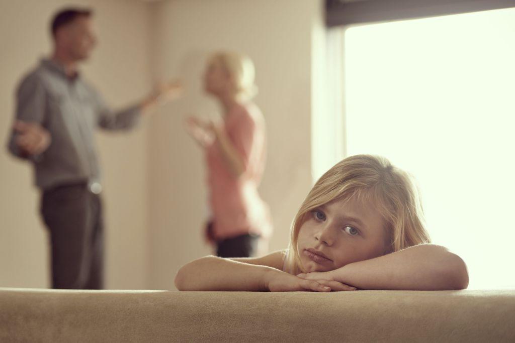 En liten jente ser trist inn i kameraet, mens foreldrene krangler i bakgrunnen