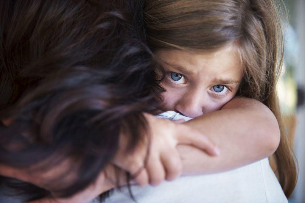 Advokat barnevern: Trist jente omfavner mamma og ser inn i kamera
