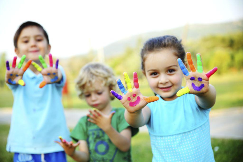 3 barn har malt hendene sine og viser de fornøyd frem