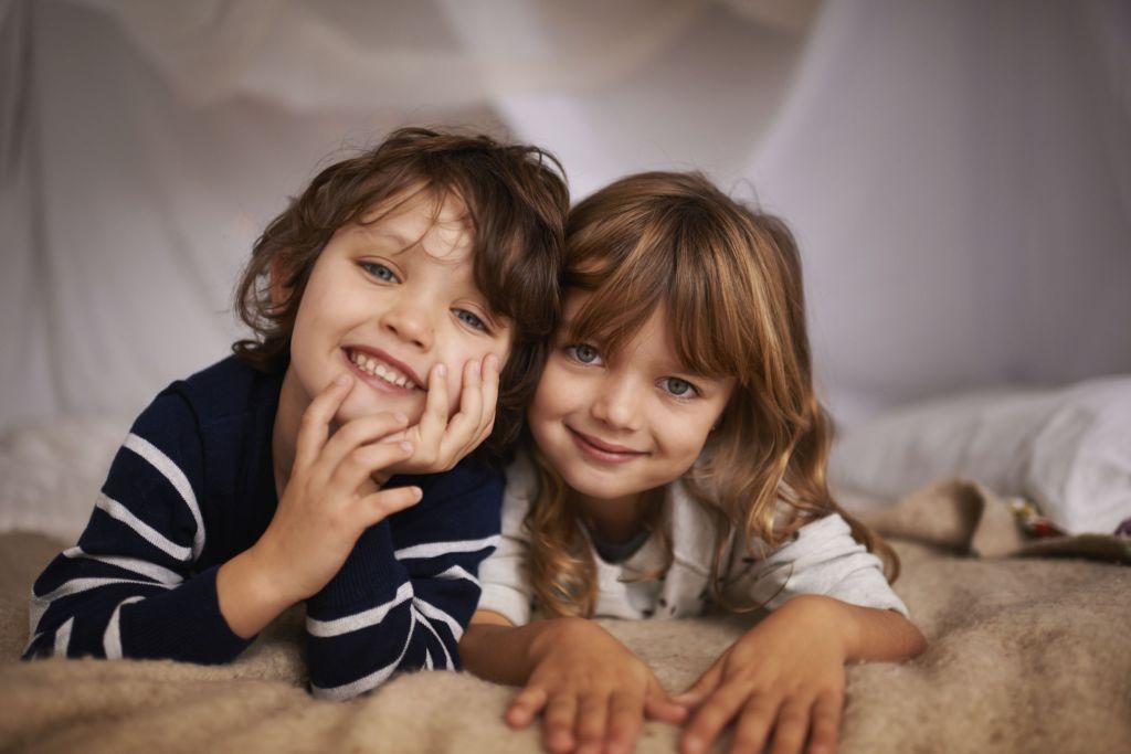 2 små barn, bror og søster, ligger på et pledd og ser inn i kameraet